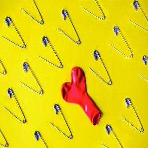 Open safety pin and red deflated ballon on yellow background